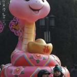 A mother holding her child poses for a photo next to a snake sculpture in Beijing