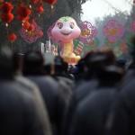 Security guards walk towards a snake sculpture in Beijing