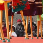 People watch Chinese folk artists on stilts during their performance at Longtan Park in Beijing
