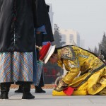 A performer dressed as a Qing dynasty emperor bows while he prays in an ancient Qing Dynasty ceremony during the temple fair at Ditan Par in Beijing