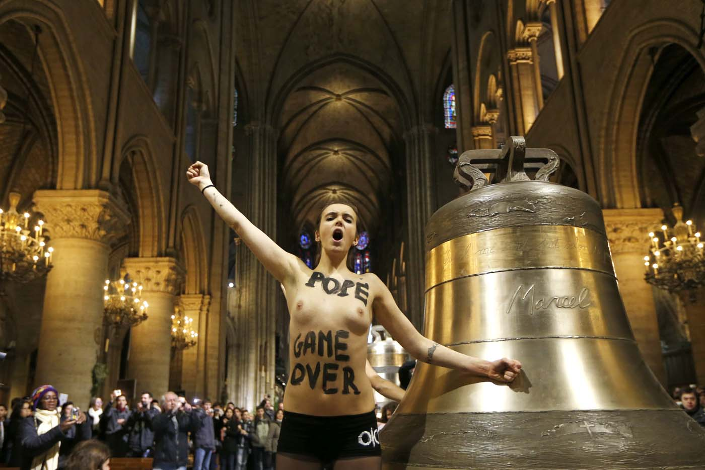 An activist from the women's rights organisation Femen protests in front of the new eight bronze bells displayed in the nave of Notre-Dame de Paris Cathedral in Paris