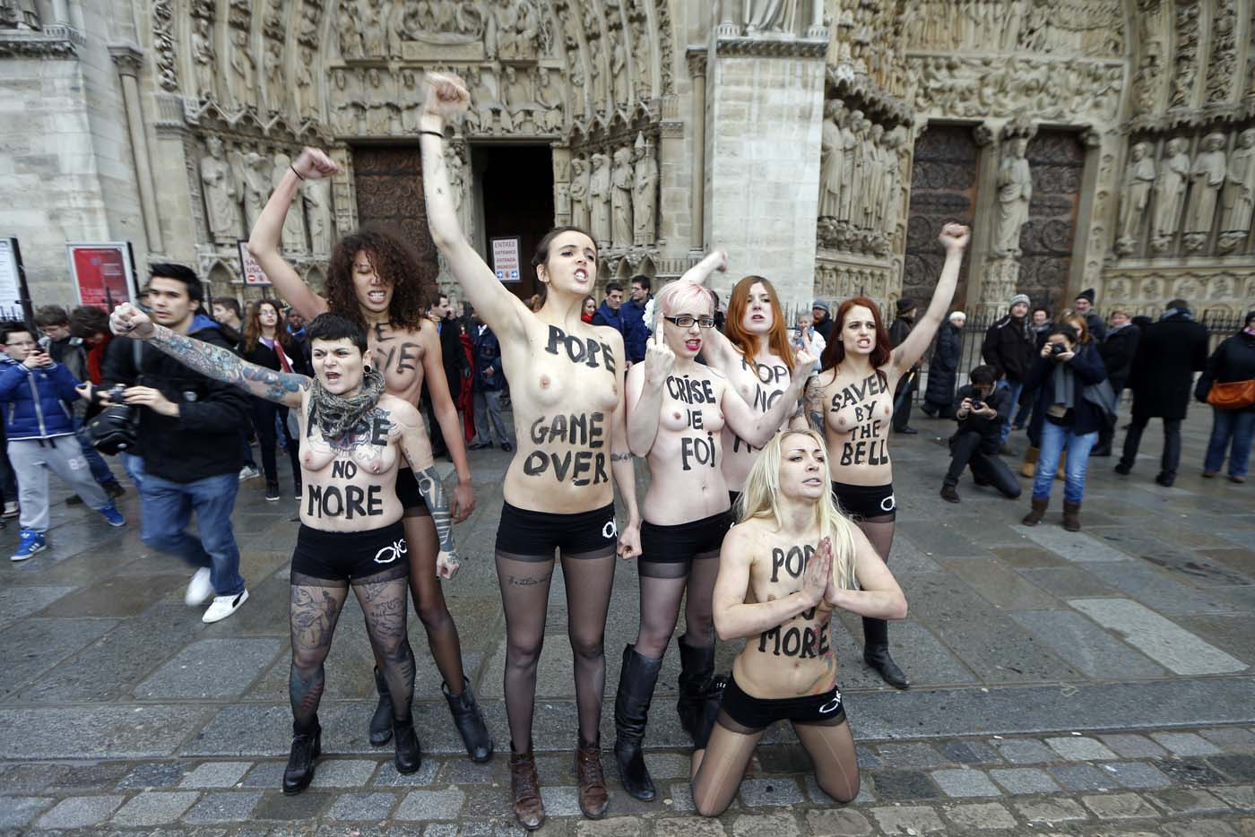 Activists from the women's rights organisation Femen shout slogans outside Notre-Dame de Paris Cathedral  in Paris