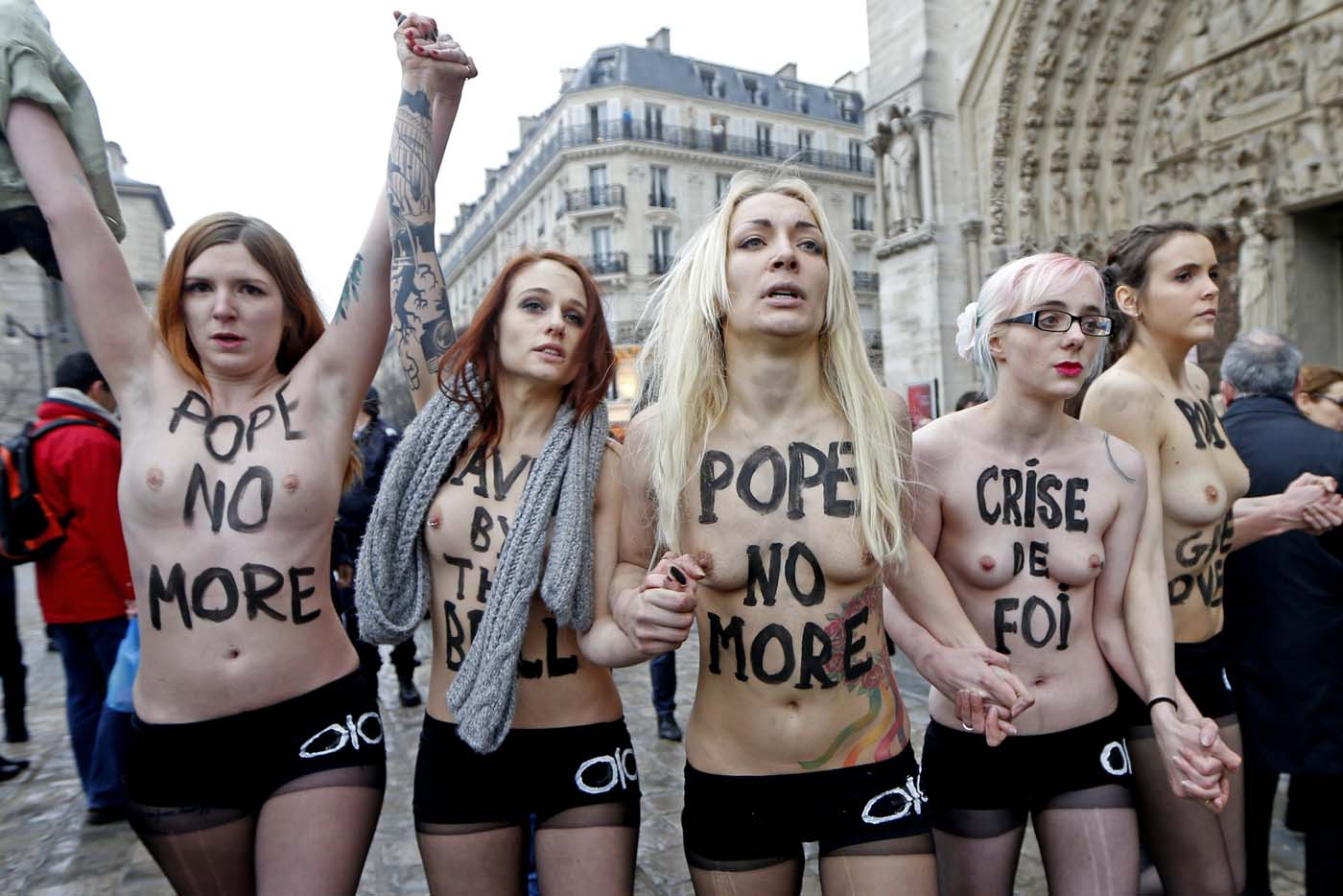 Activists from the women's rights organisation Femen leave Notre-Dame de Paris Cathedral after a protest in Paris