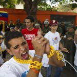 Venezuelan students chain themselves together as they take part in demonstration near Cuban embassy in Caracas
