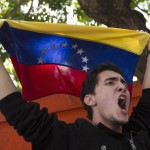 Venezuelan student waves a Venezuelan flag during a demonstration near the Cuban embassy in Caracas