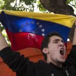 Venezuelan student waves a Venezuelan flag during a demonstration near the Cuban embassy in Caracas