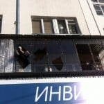 Man removes shards of glass from the frame of a broken window following sightings of a falling object in the sky in the Urals city of Chelyabinsk
