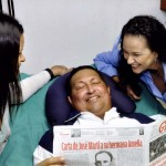 Venezuela's President Chavez holds a copy of the newspapers while recovering from cancer surgery in Havana