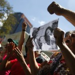 Supporters of Venezuelan President Chavez hold a copy of a photograph of Chavez as they take part in a gathering at Plaza Bolivar in Caracas
