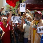 Supporters of Venezuelan President Chavez hold copies of a photograph of Chavez as they take part in a gathering at Plaza Bolivar in Caracas
