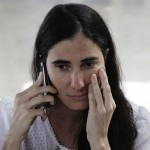 Cuba's best-known dissident, blogger Yoani Sanchez, uses a mobile phone at Havana's Jose Marti International Airport