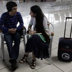 Cuba's best-known dissident, blogger Yoani Sanchez, talks with her son Teo Escobar before checking in at Havana's Jose Marti International Airport