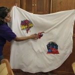 A woman activates the light on an applique with the image of cartoon character Spiderman after touching it on Catholic priest Alvarez's robe at Ojo de Agua church in Saltillo