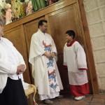 An altar boy looks at Catholic priest Humberto Alvarez's robe before Alvarez officiates mass for the congregation at Ojo de Agua church in Saltillo