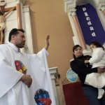 Catholic priest Alvarez blesses the faithful while wearing a robe with the images of cartoon characters Superman and Batman at the Ojo de Agua church in Saltillo