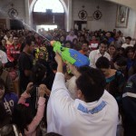 Catholic priest Alvarez sprays holy water from a water gun to bless the faithful during a mass at the Ojo de Agua church in Saltillo