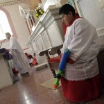An altar boy holds a water gun while Catholic priest Alvarez officiates mass at the Ojo de Agua church in Saltillo