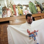 Catholic priest Alvarez holds up his robe with images of cartoon character Superman before officiating mass at Ojo de Agua church in Saltillo