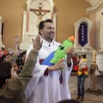 Catholic priest Alvarez sprays holy water from a water gun to bless the children during a mass at the Ojo de Agua church in Saltillo