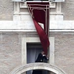 Pope Benedict XVI's personal secretary Georg Gaenswein starts to remove the tapestry at the end of his last Angelus prayer before stepping down in Saint Peter's Square at the Vatican