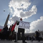 "A man holds holds a placard which reads ""Dear Pope, we'll miss you"" during Pope Benedict XVI' s Angelus in Saint Peter's Square at the Vatican"