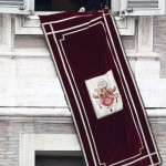 Pope Benedict XVI's personal secretary Georg Gaenswein removes the tapestry at the end of his last Angelus prayer before stepping down in Saint Peter's Square at the Vatican
