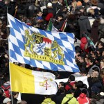 Faithful hold the Bavarian and Vatican flags as Pope Benedict XVI leads his last Angelus prayer before stepping down in Saint Peter's Square at the Vatican