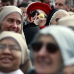 A woman uses binoculars as she stands among nuns during Pope Benedict XVI's last Angelus in Saint Peter's Square at the Vatican