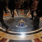 Faithful walk on the coat of arms of Pope John Paul II  in Saint Peter Basilica at the Vatican