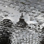 The dome of Saint Peter's Basilca is reflected in a water puddle while workers prepare the weekly audience of Pope Benedict XVI in Saint Peter's Square at the Vatican