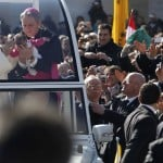 Pope Benedict XVI blesses a baby as he rides around St Peter's Square to hold his last general audience at the Vatican