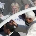 Pope Benedict XVI waves from his Popemobile as he rides through a packed Saint Peter's Square at the Vatican during his last general audience