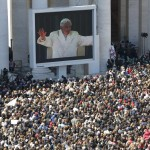 Pope Benedict XVI appears on a giant screen in a packed Saint Peter's Square at the Vatican during his last general audience
