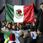 Priests hold a Mexican flag in St Peter's Square before Pope Benedict XVI's last general audience at the Vatican