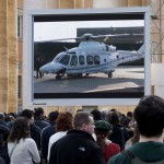 People watch a giant screen of the helicopter waiting to carry Pope Benedict XVI  to the papal summer residence at Castelgandolfo
