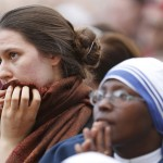 People react near a giant screen showing the departure of Pope Benedict XVI  from the Vatican City
