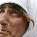 A woman reacts near a giant screen showing the departure of Pope Benedict XVI  from the Vatican City