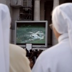 Nuns watch a giant screen of the helicopter carrying Pope Benedict XVI  to the papal summer residence at Castelgandolfo