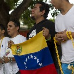 Venezuelan students pray as they chain themselves to each other during a demonstration near the Cuban embassy in Caracas