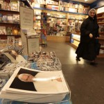 A nun walks past pictures of Pope Benedict XVI in a souvenir shop near Saint Peter's Square at the Vatican