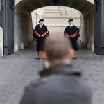 A man takes a picture of Swiss Guards standing at the entrance of the Vatican