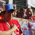 Supporters of deceased Venezuelan leader Hugo Chavez react as his coffin is driven through the streets of Caracas