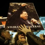 A woman cries as she holds a picture of late Venezuelan President Hugo Chavez during a rally to pay him homage in Madrid