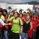 Supporters of Venezuela's late President Hugo Chavez protest over others cutting the line as they wait to view his body in state at the Military Academy in Caracas