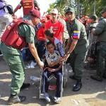 A wheelchair-bound supporter of Venezuela's late President Hugo Chavez is assisted towards the Military Academy to view his body in state in Caracas