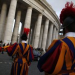 Swiss guards stand guard in front of the gate where Cardinals arrive to attend a meeting at the Synod Hall in the Vatican