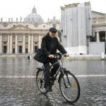 French Cardinal Philippe Barbarin rides his bicycle through Saint Peter's square after a meeting at the Synod Hall at the Vatican