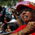A supporter of Venezuela's late President Chavez reacts as she waits for a chance to view his body lying in state in Caracas