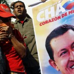 A supporter of Venezuela's late President Hugo Chavez reacts next to a portrait of him as she waits for a chance to view his body lying in state in Caracas