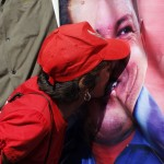 A supporter of Venezuela's late President Chavez kisses a portrait of him as she waits for a chance to view his body lying in state in Caracas